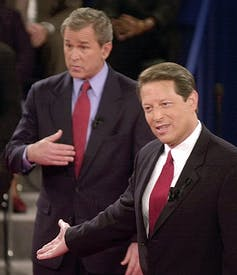 Al Gore is seen gesturing in a debate with George W. Bush, as Bush looks on with a 'who me?' expression in the background.