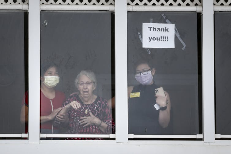 An elderly woman, flanked by two long-term health-care workers wearing masks, looks out a window and waves.