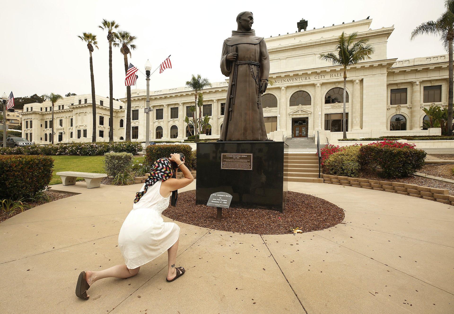 woman photographing Junipero Serra statue