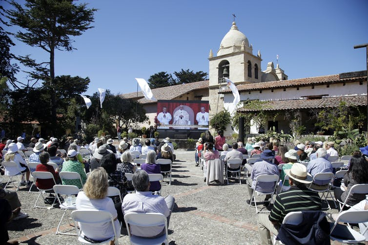 A crowd watches Pope Francis on a screen outside a Spanish colonial building