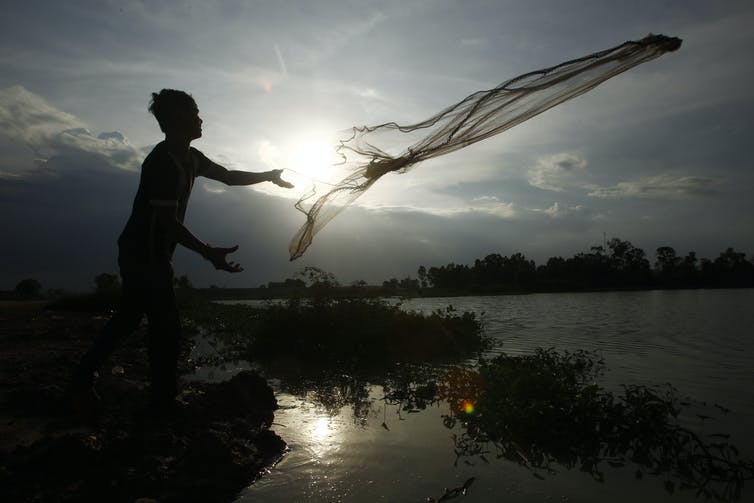 A man tosses a fishing net into a body of water with the sun rising in the background.