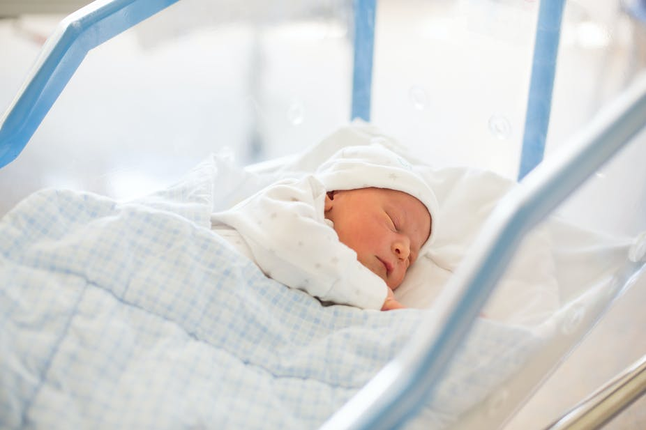 Newborn baby sleeps in a hospital crib