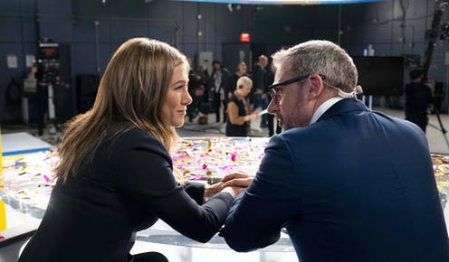 Jennifer Aniston and Steve Carell in role as news anchors hold hands in a still from 'The Morning Show.'