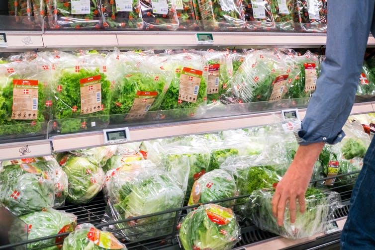 A person's arm reaches for a package of greens from a selction of greens and lettuces in a grocery story.