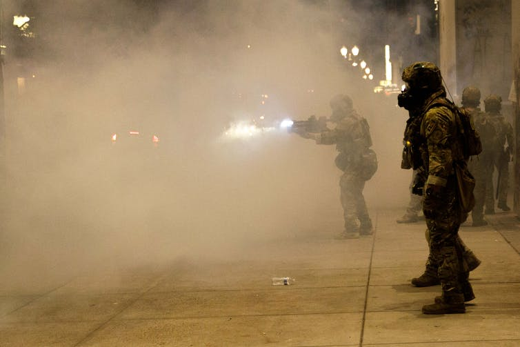 A federal officer in a heavy camouflage uniform fires into a cloud of smoke
