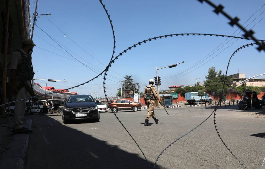 Policeman on street behind barbed wire