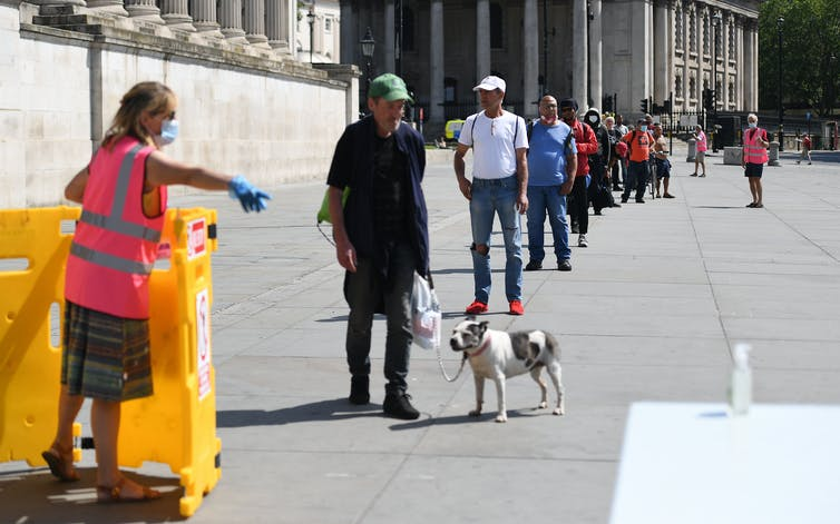 Homeless people queue for food in Trafalgar Square, London.