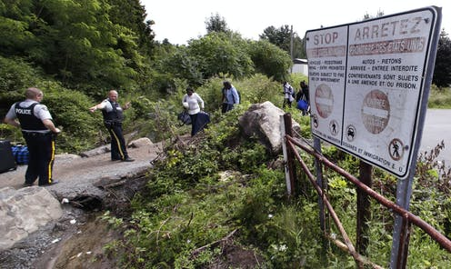Police officers direct a group of migrant walking along a rocky path, with trees in the background and a warning sign to the right of the scene.