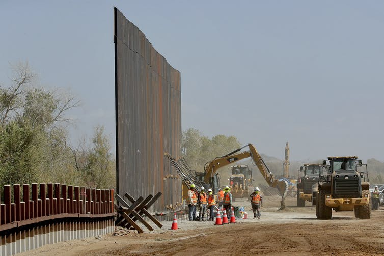 A tall portion of metal wall stands as construction workers work at its base, with a bulldozer and tractors in the background.