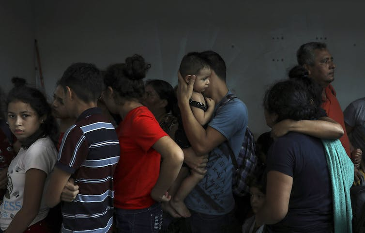 A group of migrants, including a man holding a small baby, are seen standing together in a darkened room. One teenaged girl looks directly at the camera.