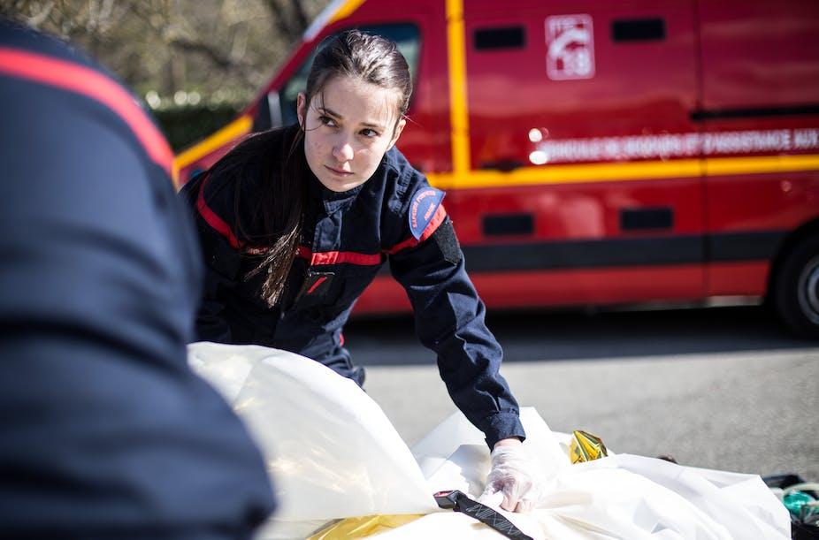 Une sapeuse-pompière des Bouches-du-Rhône prend en charge une victime au cours d'une opération sanitaire avec son équipe.