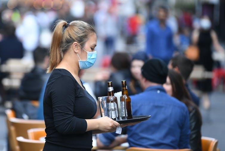 A waitress wearing a facemask serving drinks at a bar.