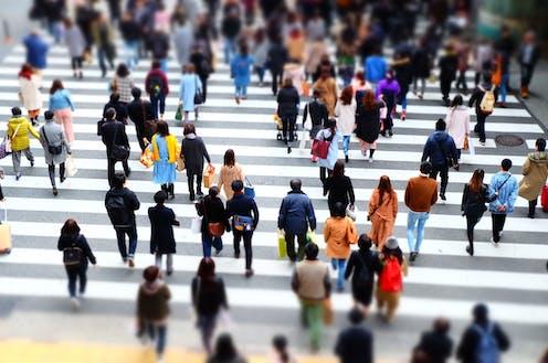 Many people walking across a road crossing in a city.