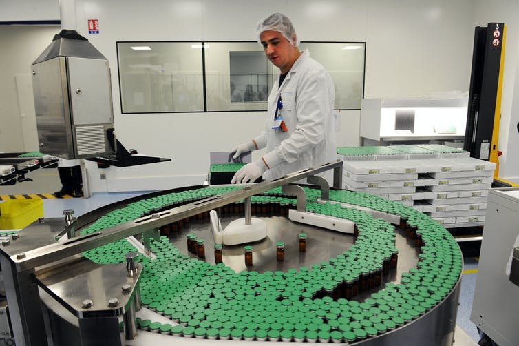 A man overseeing the production of doses of flu vaccine.