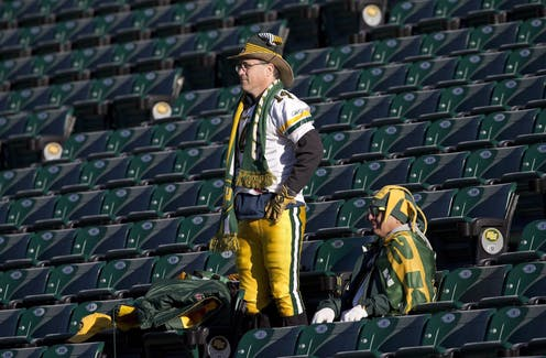 Two fans of Edmonton's CFL team in the stands watching a team practice, while wearing team merchandise.