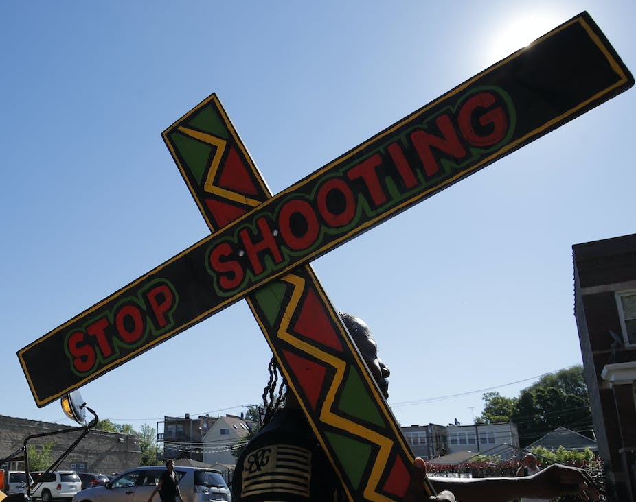 Woman carries cross reading 'stop shooting'