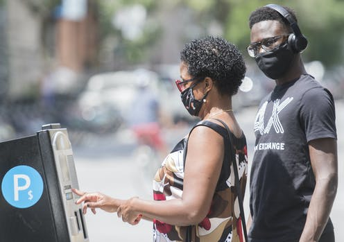 Two people wear face masks as they pay for parking