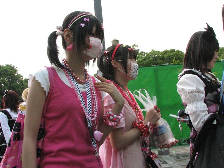 Two Japanese Harajuku girls in pink dresses wear face masks.