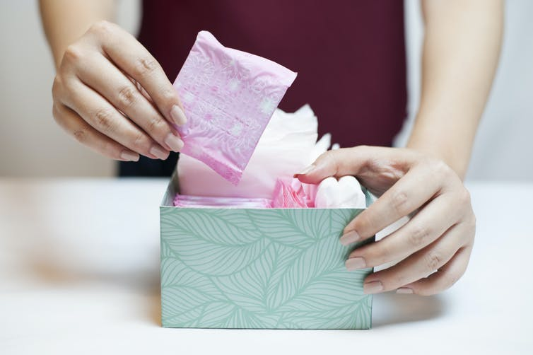 A woman choosing a sanitary pad from a box containing sanitary items.