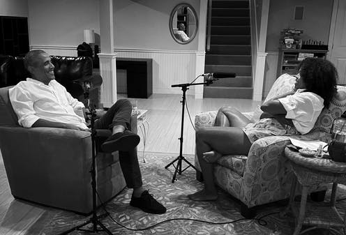 Barack and Michelle Obama sit in armchairs, recording a podcast.