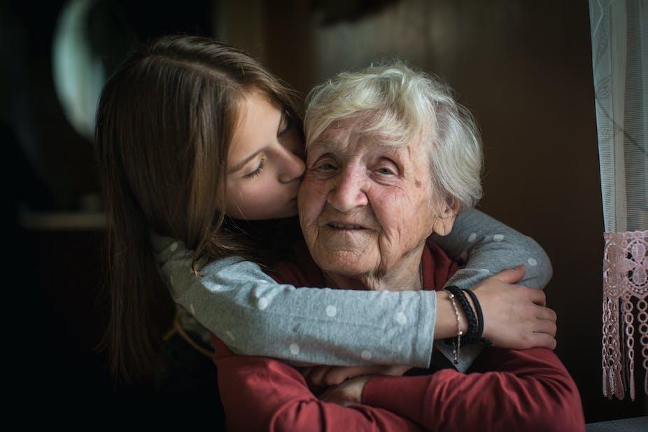 Girl kisses her grandma on the cheek.