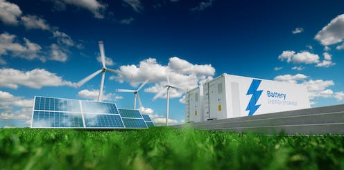 Solar panels, wind turbines and large batteries in field.