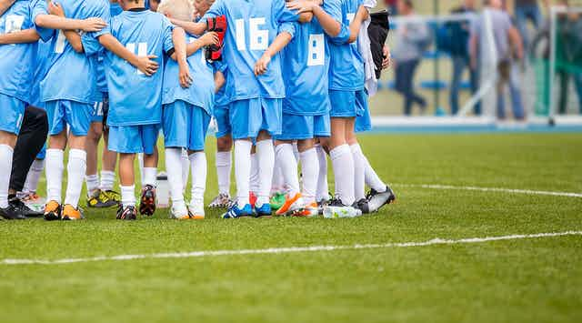 equipo de fútbol infantil abrazándose