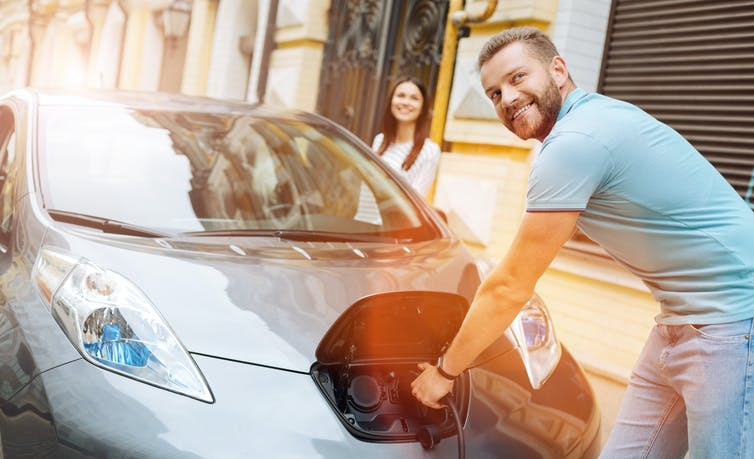 Smiling man plugs in electric car.