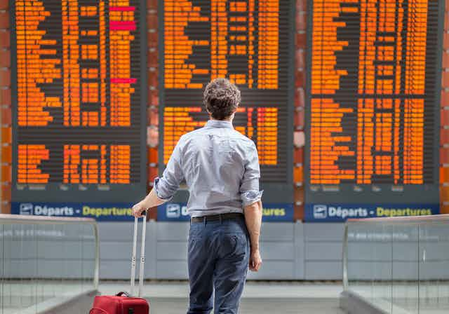 A man stands before an airport departure board.