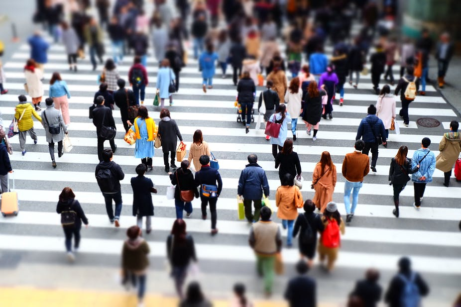Orang banyak berjalan di persimpangan jalan di kota.
