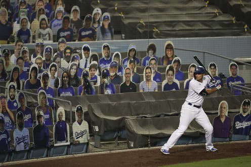 A baseball player swings a bat in front of stadium seats filled with cutouts of fake fans.