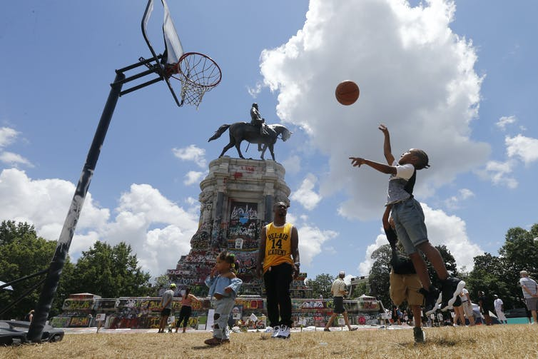 A young Black girl plays basketball at a makeshift court in front of the Robert E. Lee statue, covered in anti-racist graffit, in Richmond, Va.