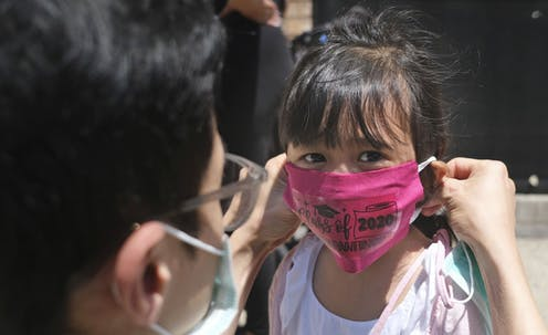 A father puts a pink face mask on his young daughter.