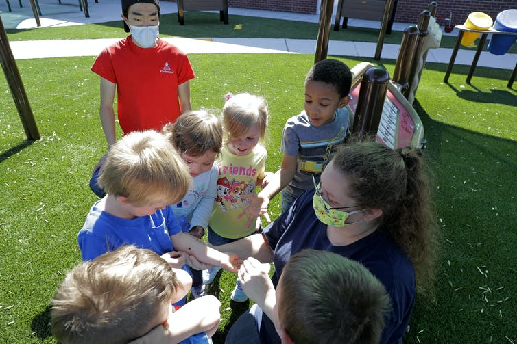 A group of kids without masks gather around a teacher wearing a mask outside.