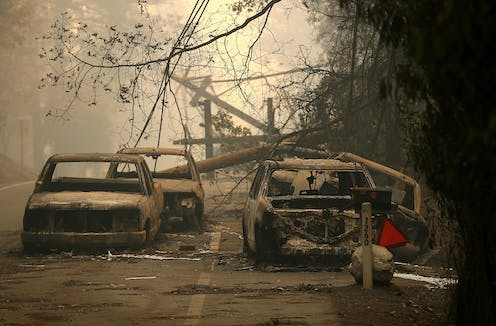 Burned cars and downed trees after the Camp wildfire