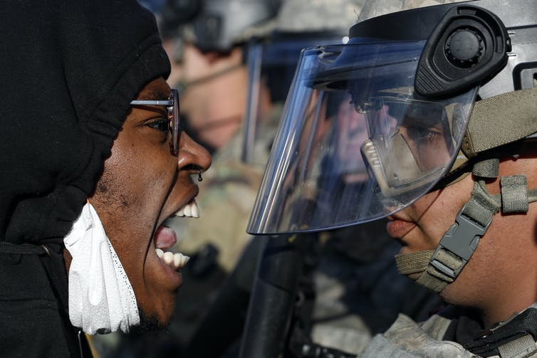 A Black protestor shouts at a national guardsman, wearing fatigues and a face shield, during a protest