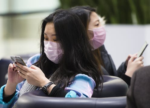 Two Asian women wearing face masks sit on couches while using their phones.