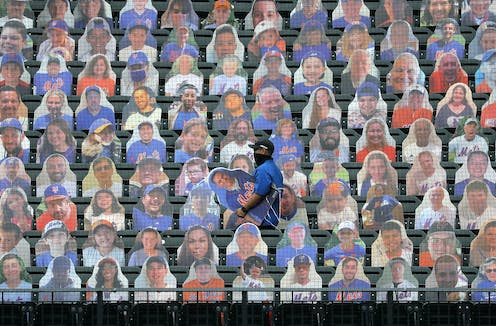 An employee of the New York Mets baseball team carries a cardboard cutout of a fan that will be placed in the empty stands.