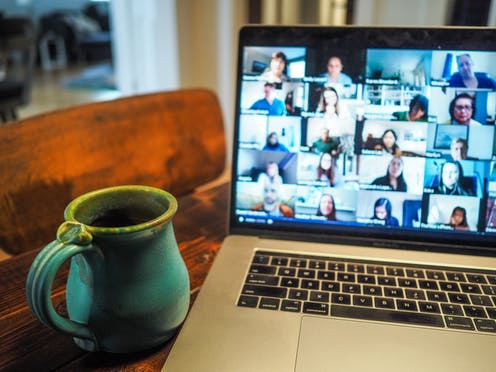 Several faces are shown on a laptop screen with a blue mug of coffee in the foreground.