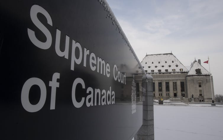 A sign reads Supreme Court of Canada with the Supreme Court buildings in the background with snow on the ground.