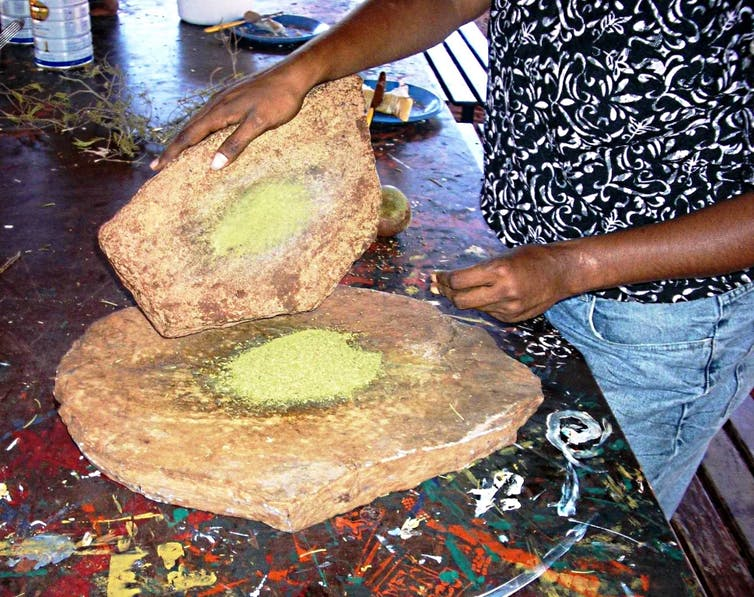 An indigenous person grinding native grain.