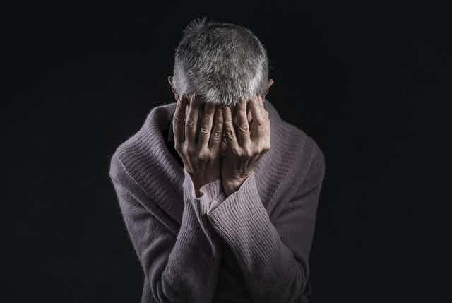 Despairing grey-haired women holds her head in her hands