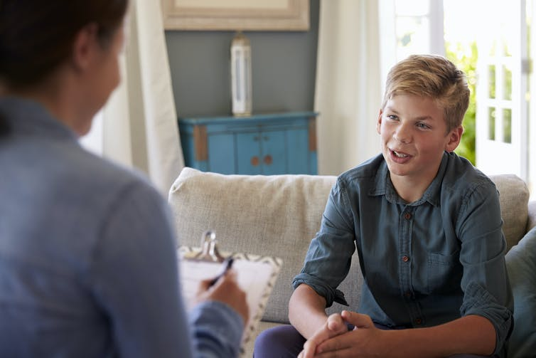 Young teenage boy sits on couch talking with counsellor.