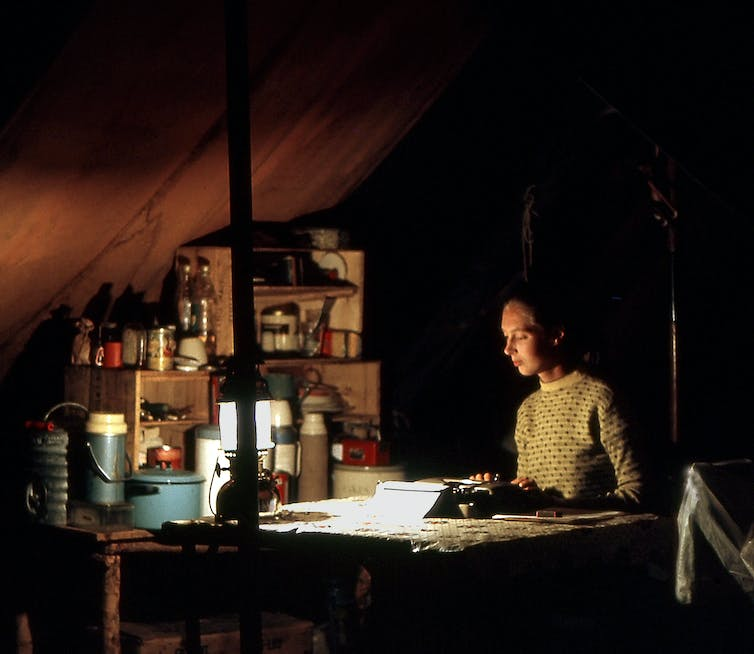 A young Jane Goodall writes notes on her desk in a tent by the dim light of a small lamp.