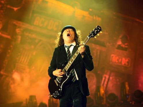 AC/DC Andy Young playing guitar in school uniform.