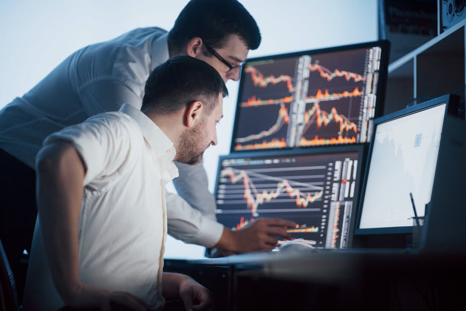Two stockbrokers look at data on screens.