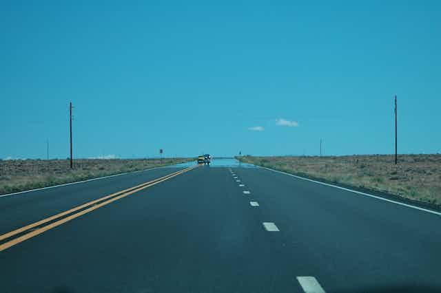 Un mirage sur une route chauffée par le soleil