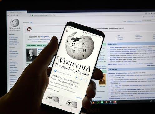 Una mano sujeta un móvil con la página de la Wikipedia. De fondo, página Wikipedia en pantalla de ordenador