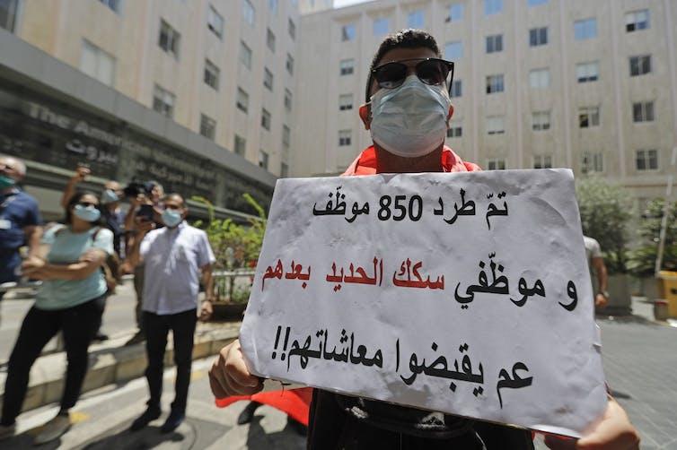 manifestant pancarte licenciements beyrouth crise