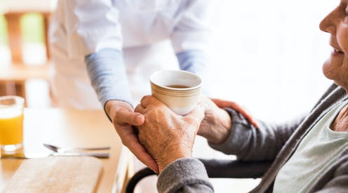 Carer gives patient a drink